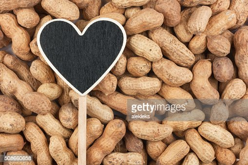 Pointer in the form of heart lies on peanut : Stock Photo