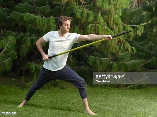 Poised young man in park practicing martial arts holding bo staff