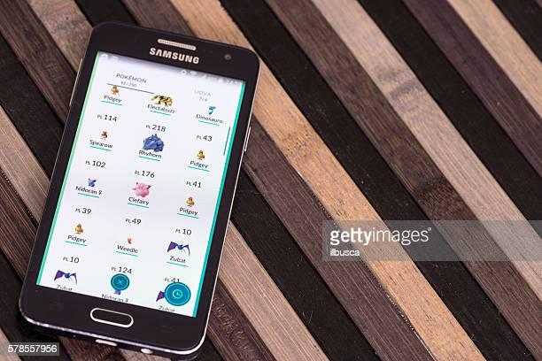 Pokemon go on Samsung smartphone on striped wood table