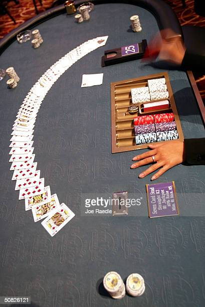 A poker dealer lays the cards on the table May 11 2004 during the grand opening for the Seminole Hard Rock Hotel and Casino in Hollywood Florida...
