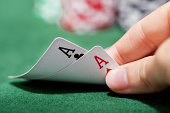 Hand of a male poker player lifting the corners of two cards on the green felt checking a pair of aces