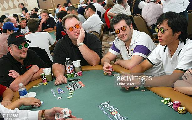 Poker player Greg 'Fossilman' Raymer the 2004 World Series of Poker champion competes as other players Keith Plemons Fabio Cunha and Artit Soh wear...