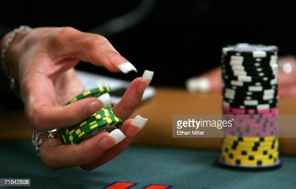 Poker player Liz Lieu plays with her chips as she competes on the third day of the first round of the World Series of Poker nolimit Texas Hold 'em...