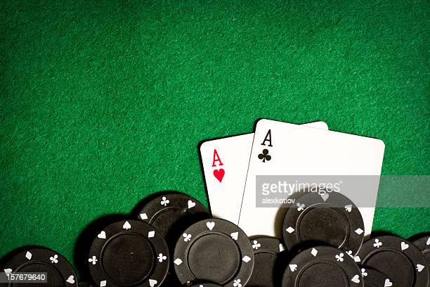 Poker table with black gambling chips and aces