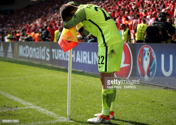 Poland goalkeeper Lukasz Fabianski hides behind the corner flag as the final penalty is taken in the shootout by teammate Grzegorz Krychowiak