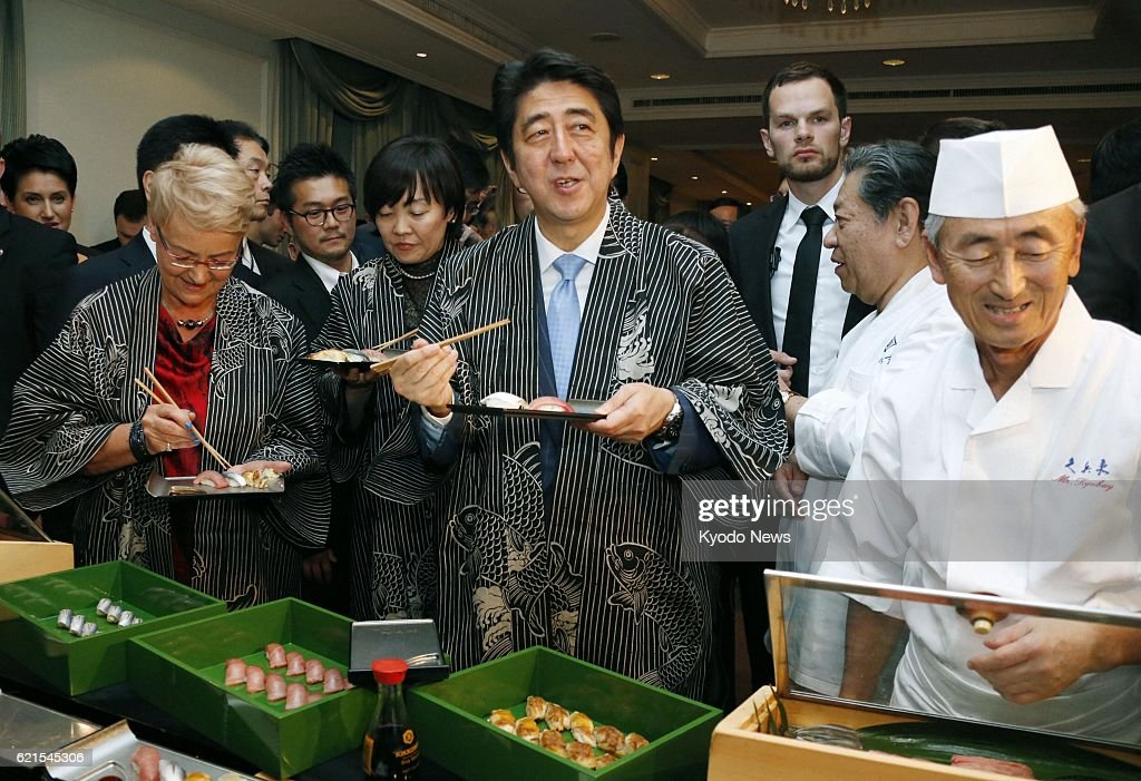 WARSAW, Poland - Japanese Prime Minister Shinzo Abe (C) eats sushi at a reception to introduce Japanese food culture in Warsaw, Poland, on June 15, 2013.