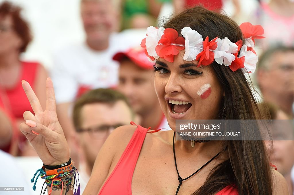 A Poland supporter flashes the V-sign prior to the Euro 2016 quarter-final football match between Poland and Portugal at the Stade Velodrome in Marseille on June 30, 2016. / AFP / ANNE