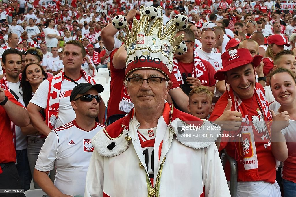 A Poland supporter stands with others prior to the Euro 2016 quarter-final football match between Poland and Portugal at the Stade Velodrome in Marseille on June 30, 2016. / AFP / ANNE