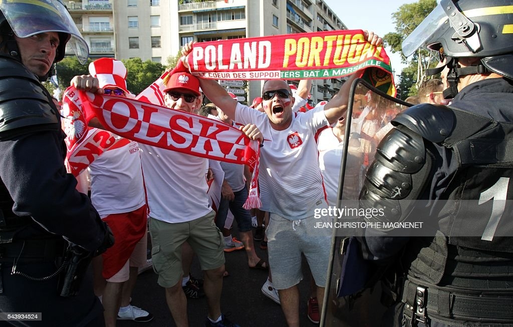 Poland supporters cheer in front of the anti riot police prior to the Euro 2016 championship match between Poland and Portugal, in Marseille, southern France, on June 30, 2016. / AFP / JEAN