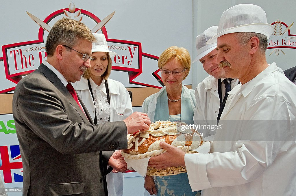 Poland's acting President Bronislaw Komorowski (L) takes a piece of bread to eat, during a visit to the Polish Bakery in west London on 2 June, 2010. Komorowski, the frontrunner in Poland's forthcoming elections, is on a whistle stop visit to the UK. AFP PHOTO/Leon Neal