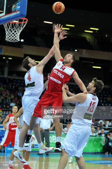 Poland's Adam Hrycaniuk jumps after a ball between Pau and Marc Gasol of Spain during the first round EuroBasket2011 group A qualification match...