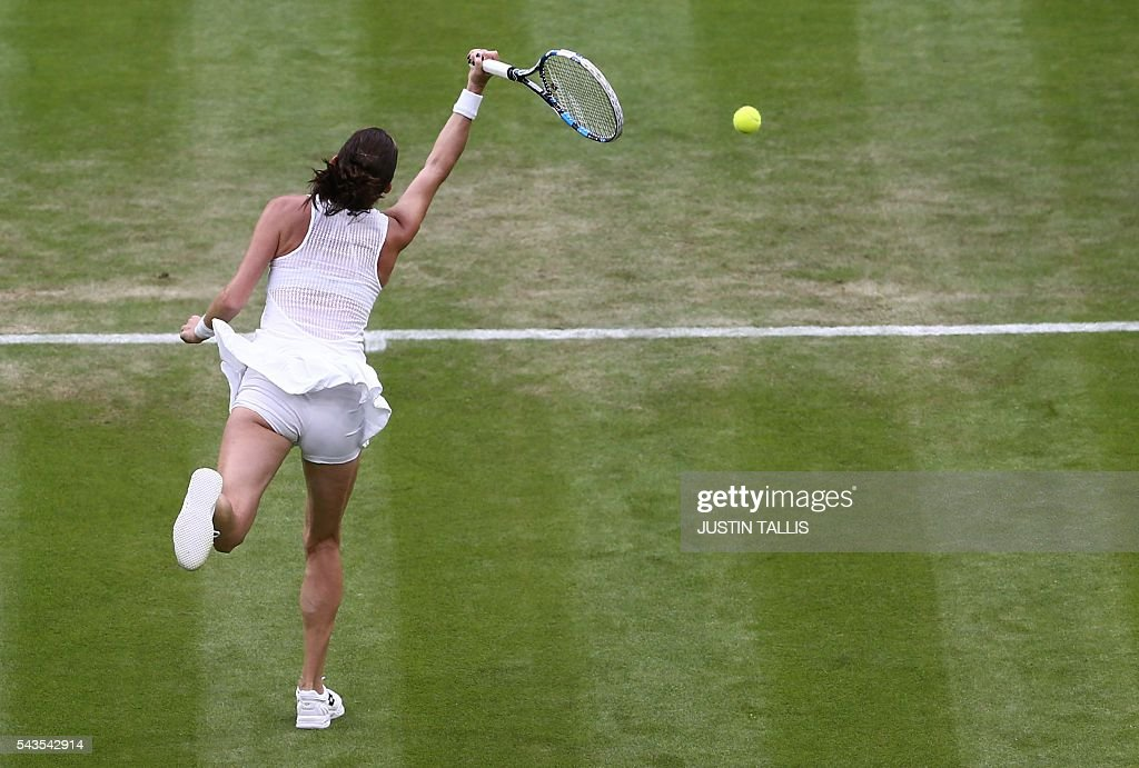 Poland's Agnieszka Radwanska jumps for a return against Ukraine's Kateryna Kozlova during their women's singles first round match on the third day of the 2016 Wimbledon Championships at The All England Lawn Tennis Club in Wimbledon, southwest London, on June 29, 2016. / AFP / JUSTIN