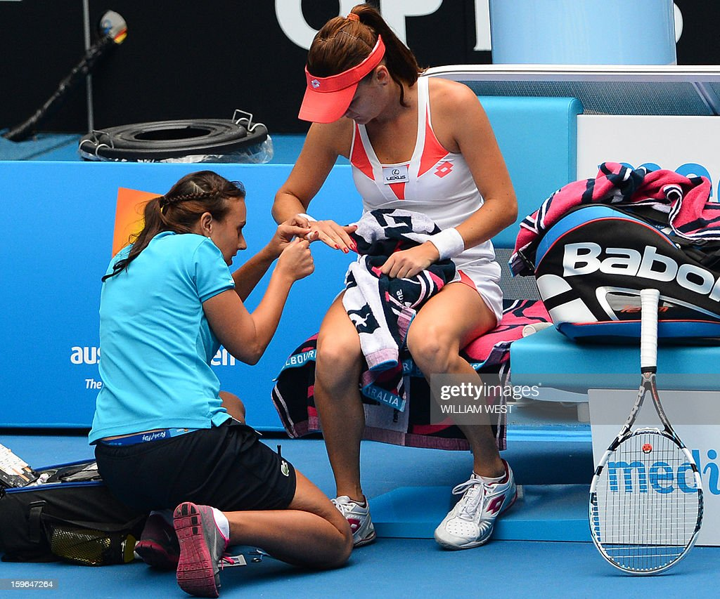 Poland's Agnieszka Radwanska (R) receives treatment from a trainer during her women's singles match against Heather Watson of Britain on the fifth day of the Australian Open tennis tournament in Melbourne on January 18, 2013.
