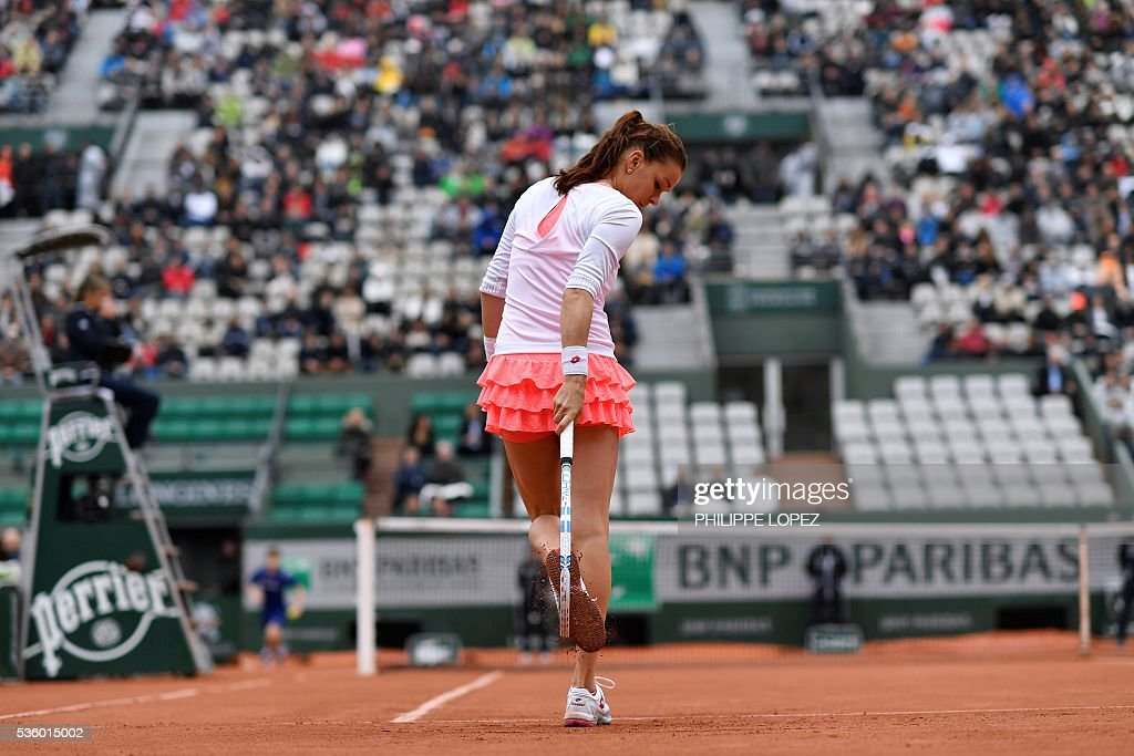 Poland's Agnieszka Radwanska removes clay from her shoes during her women's fourth round match against Bulgaria's Tsvetana Pironkova at the Roland Garros 2016 French Tennis Open in Paris on May 31, 2016. / AFP / PHILIPPE