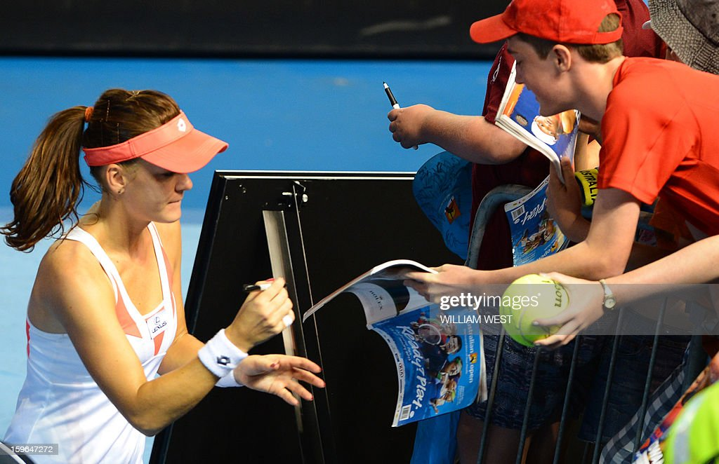 Poland's Agnieszka Radwanska (L) signs autographs after victory in her women's singles match against Heather Watson of Britain on the fifth day of the Australian Open tennis tournament in Melbourne on January 18, 2013.