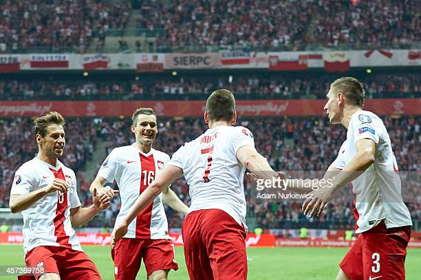 Poland's Arkadiusz Milik celebrates with teammates after scoring during the UEFA EURO 2016 qualifying match between Poland and Scotland on October 14...