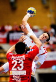 Poland's Bartlomiej Jaszka shoots next to Serbia's Nenad Vuckovic during the 22nd men's Handball World Championship Group match in Lund on January 23...