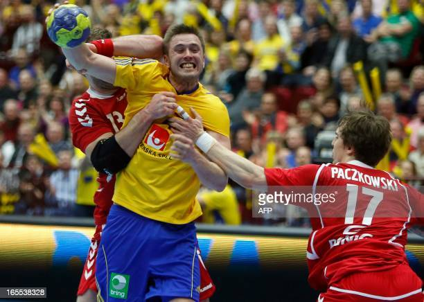 Poland's Bartosz Jurecki and Pavel Paczkowski try to stop Sweden's Jonas Larholm during the men's European Handball Championships qualification match...