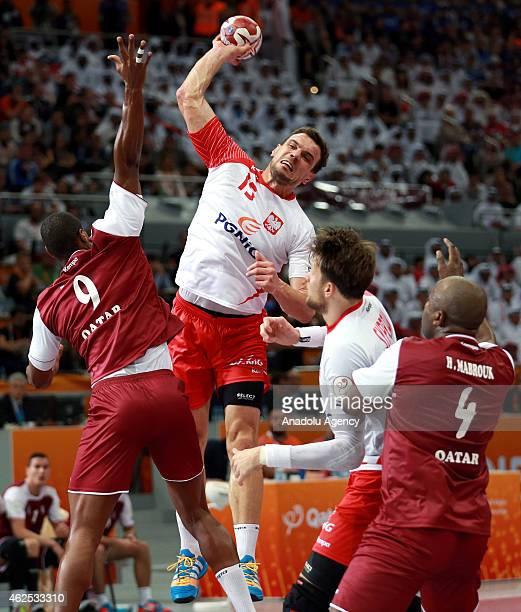 Poland's Bartosz Jurecki vies for ball with Qatar's Andrzej Rojewski during the 24th Men's Handball World Championships semifinal handball match...