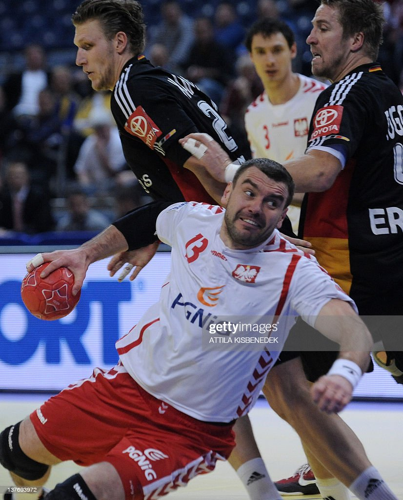 Poland's Bartosz Jurecki (down) vies with Germany's Oliver Roggisch (R) and Lars Kaufmann during the Men's EHF Euro 2012 Handball Championship match Poland vs Germany on January 25, 2012 at the Belgrade Arena.