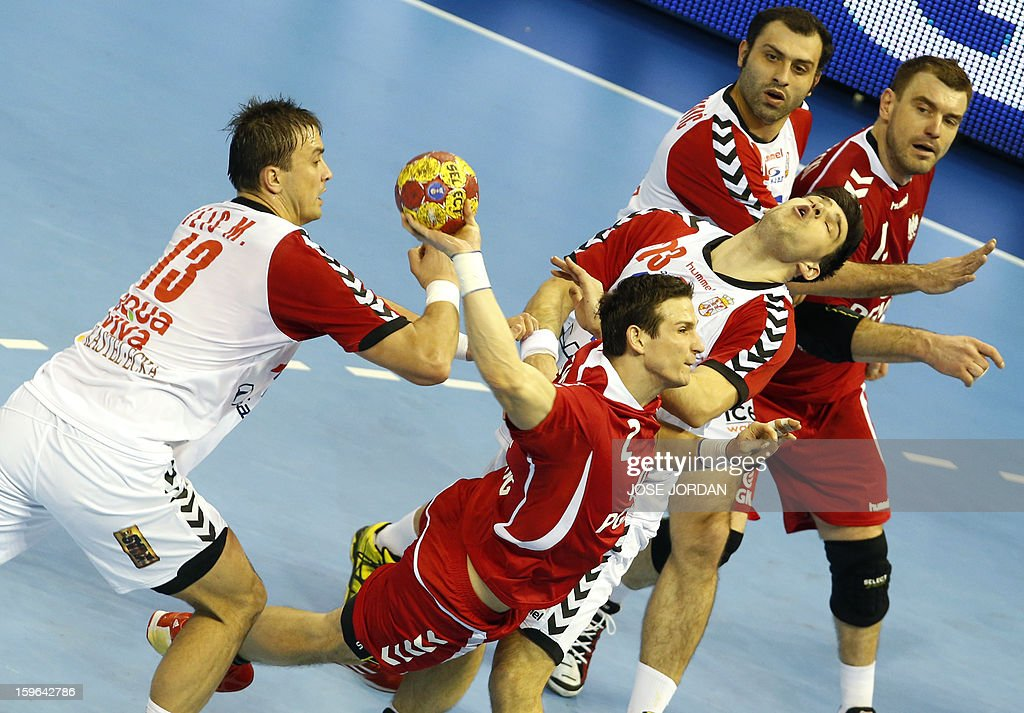 Poland's centre back Bartlomiej Jaszka (BottomC) shoots past Serbia's left back Momir Ilic (L) and Serbia's centre back Nenad Vuckovic (R) during the 23rd Men's Handball World Championships preliminary round Group C match Poland vs Serbia at the Pabellon Principe Felipe in Zaragoza on January 17, 2013.