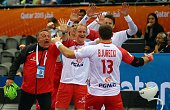 Poland's coach Michael Biegler celebrates their win with players during the 24th Men's Handball World Championships Eighth Final EF2 match between...