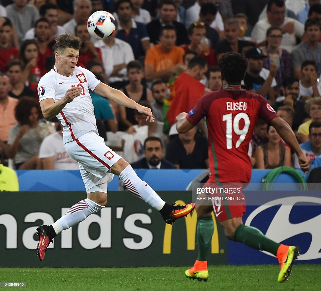 Poland's defender Lukasz Piszczek (L) vies for the ball with Portugal's defender Eliseu during the Euro 2016 quarter-final football match between Poland and Portugal at the Stade Velodrome in Marseille on June 30, 2016. / AFP / BERTRAND