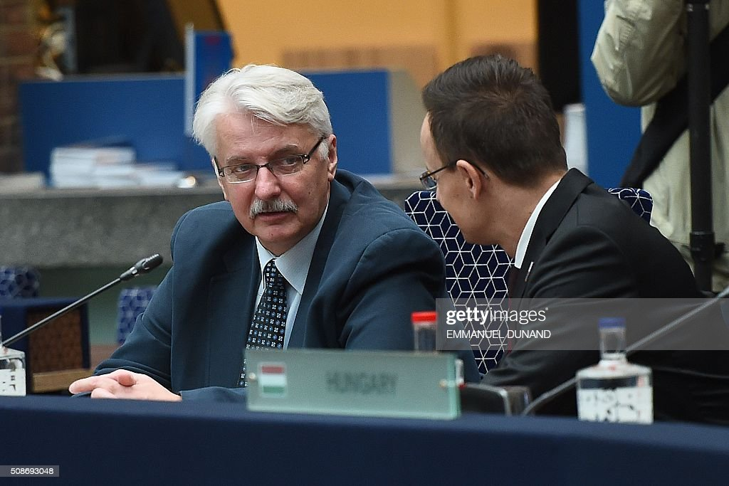 Poland's Foreign Minister Witold Waszczykowski (L) and Hungary's Foreign Minister Peter Szijjarto speak together ahead of a EU foreign ministers meeting in Amsterdam, on February 6, 2016. The European Union on Wednesday finally reached agreement on how to finance a three-billion-euro ($3.3-billion) deal to aid Syrian refugees in Turkey, in exchange for Ankara's help in stemming the flow of migrants. / AFP / EMMANUEL DUNAND