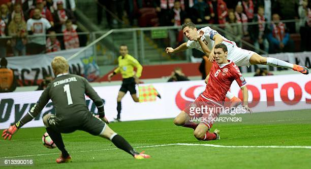 Poland's forward Robert Lewandowski scores a goal against Denmark's goalkeeper Kasper Schmeichel and Andreas Christensen during the 2018 World Cup...