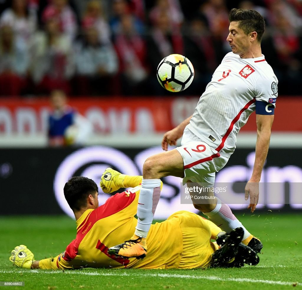 Poland's forward Robert Lewandowski (R) scores past Montenegro's goalkeeper Daniel Petkovic during the FIFA World Cup 2018 qualification football match between Poland and Montenegro in Warsaw on October 8, 2017. /
