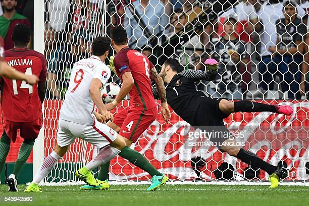 Poland's forward Robert Lewandowski scores the fist goal past Portugal's goalkeeper Rui Patricio during the Euro 2016 quarterfinal football match...