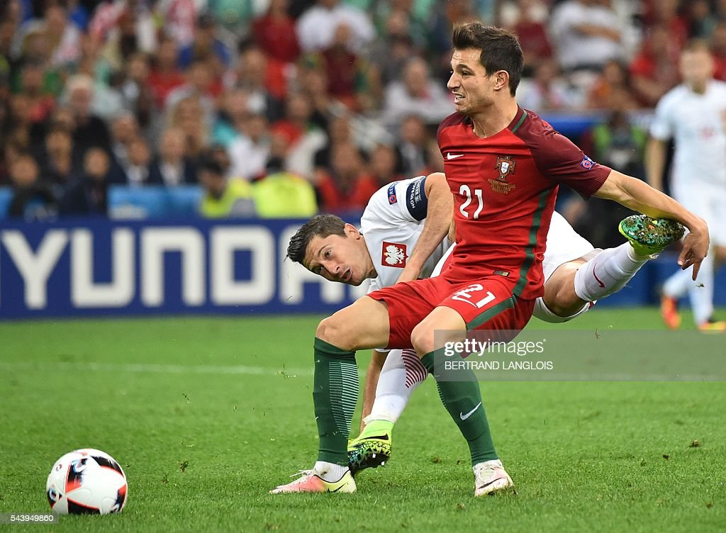 Poland's forward Robert Lewandowski (L) vies for the ball with Portugal's defender Cedric Soares during the Euro 2016 quarter-final football match between Poland and Portugal at the Stade Velodrome in Marseille on June 30, 2016. / AFP / BERTRAND