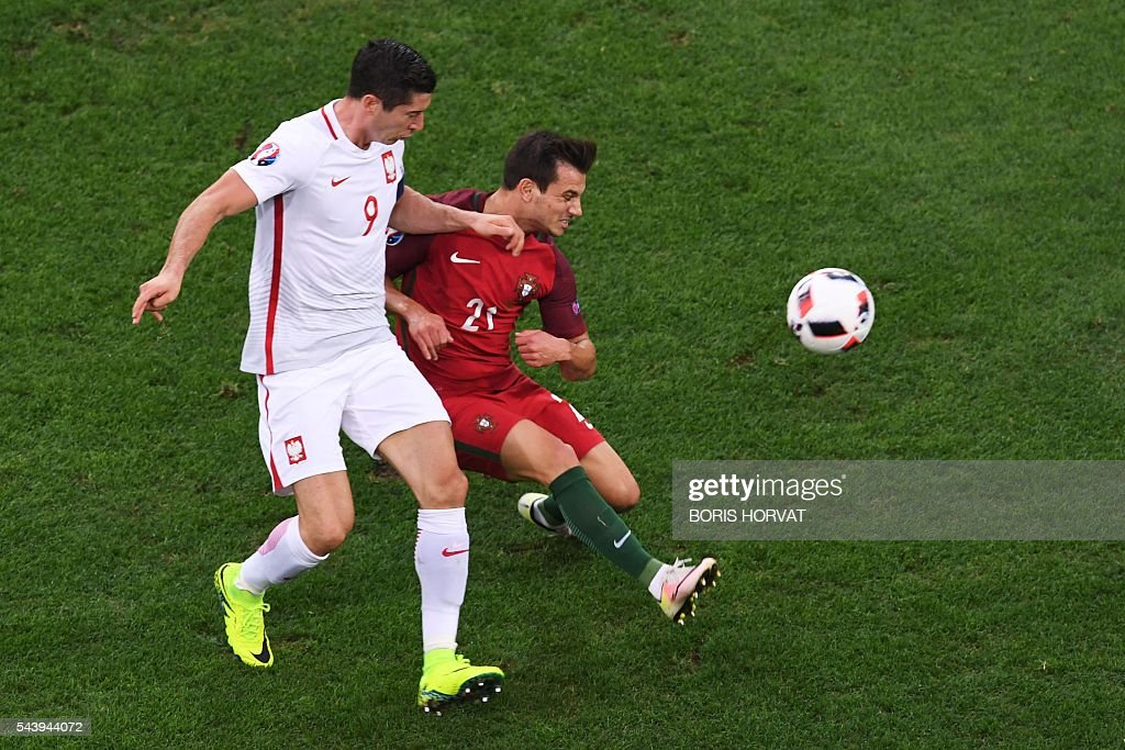 Poland's forward Robert Lewandowski (L) vies with Portugal's defender Cedric Soares during the Euro 2016 quarter-final football match between Poland and Portugal at the Stade Velodrome in Marseille on June 30, 2016. / AFP / BORIS