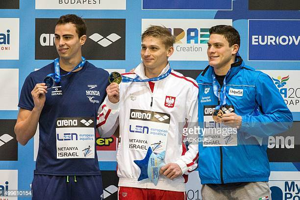 Poland's gold medalist Radoslaw Kawecki silver medalist Yakov Yan Toumarkin and Italy's bronze medalist Simone Sabbioni pose on the podium with their...