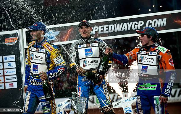 Poland's Jaroslaw Hampel celebrates with champaign after winning the Danish Speedway Grand Prix on the podium with second placed Tomasz Gollob of...