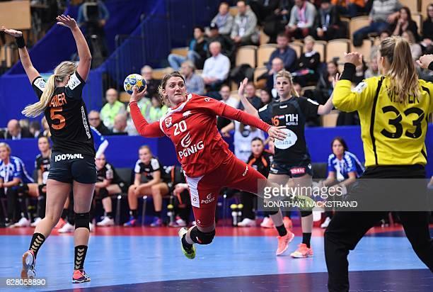 TOPSHOT Poland's Joanna Drabik prepares to throw the ball to score past Netherlands' goalkeeper Tess Wester during the Women's European Handball...