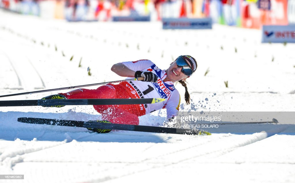 Poland's Justyna Kowalczyk slides to the ground as she comes in second on March 2, 2013 at the Women's Cross Country 30 km Classic race of the FIS Nordic World Ski Championships at Val Di Fiemme Cross Country stadium in Cavalese, northern Italy.