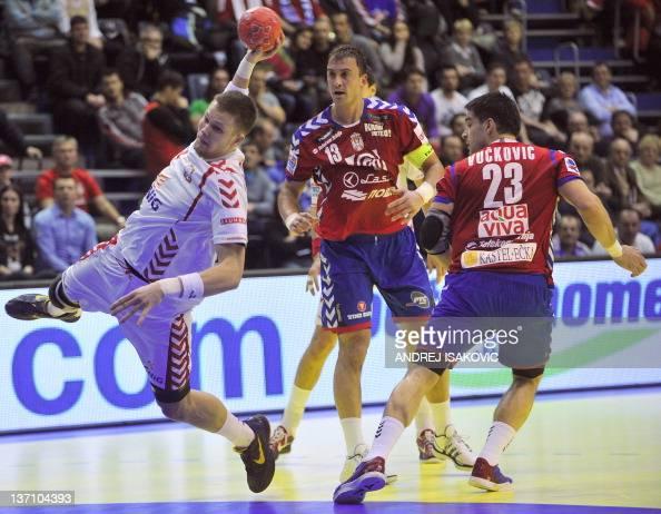 Poland's Kamil Syprzak shoots past Serbia's Momir Ilic and Nenad Vuckovic during their 10th EHF European 2012 Men's Handball Championship match at...