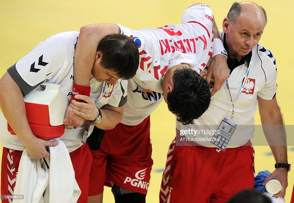 Poland's Krzysztof Lijewski (C) is carryed by his team officials after being injured during the men's EHF Euro 2012 Handball Championship match Poland vs Germany on January 25, 2012 at the Belgrade Arena. AFP PHOTO / ATTILA KISBENEDEK