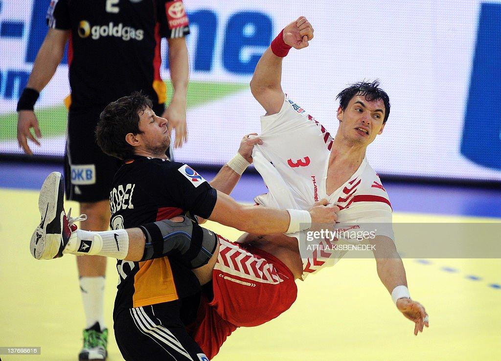 Poland's Krzysztof Lijewski (R) is pushed by Germany's Martin Strobel (L) during the men's EHF Euro 2012 Handball Championship match Poland vs Germany on January 25, 2012 at the Belgrade Arena. AFP PHOTO / ATTILA KISBENEDEK