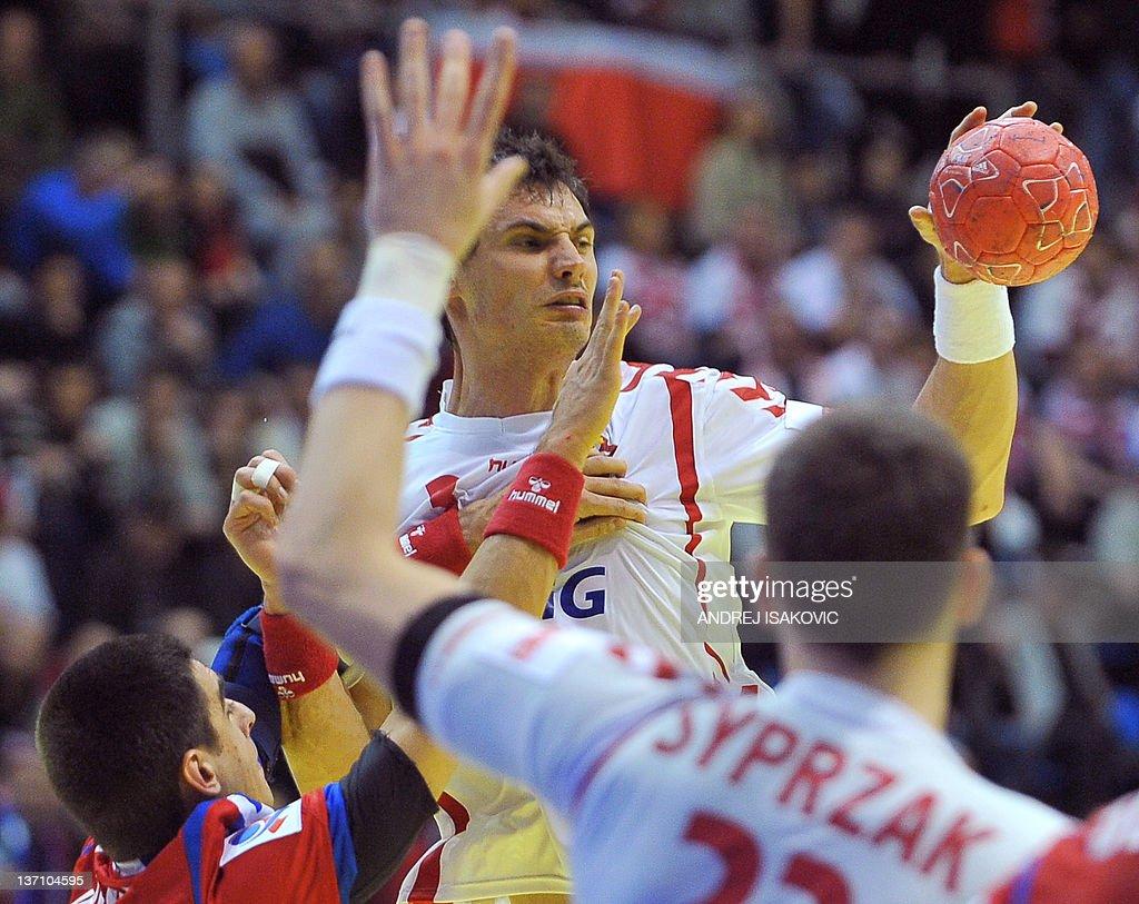 Poland's Krzysztof Lijewski (C) vies with Serbia's Bojan Beljanski (L) during their 10th EHF European 2012 Men's Handball Championship match at the Pionir Arena in Belgrade on January 15, 2012.