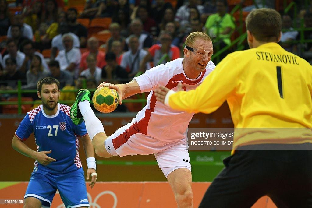 Poland's left back Karol Bielecki shoots past Croatia's right back Ivan Cupic during the men's quarterfinal handball match Croatia vs poland for the...