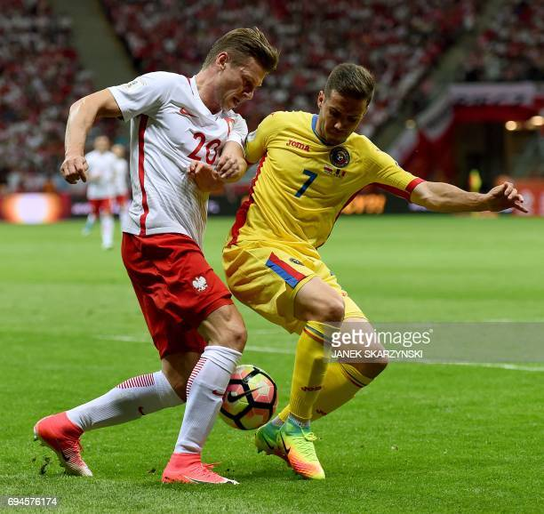 Poland's Lukasz Piszczek and Romania'sAlexandru Chipciu vie for the ball during the FIFA World Cup 2018 qualification football match between Poland...