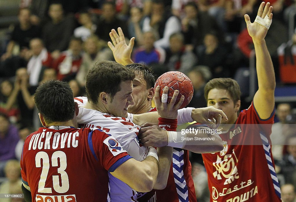 Poland's Mariusz Jurkiewicz in action against Serbia's Nenad Vuckovic (L) and Momir Ilic (R) during the Men's European Handball Championship group A match between Poland and Serbia at Pionir Sports Centre on January 15, 2011 in Belgrade, Serbia.