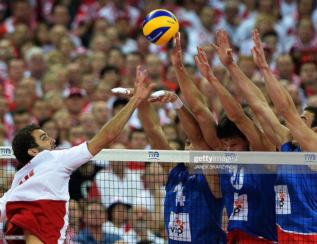 Poland's Mateusz Mika spikes against Serbia's Aleksandar Atanasijevic, Srecko Lisinac during the opening match of the FIVB Mens Volleyball World Championship at the National Stadium in Warsaw on August 30, 2014. Poland won 25 - 19, 25 - 18 , 25 - 18.