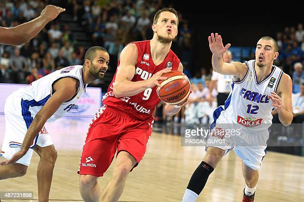 Poland's Mateusz Ponitka vies with France's Nando De Colo and France's Tony Parker during the group A qualification basketball match between France...