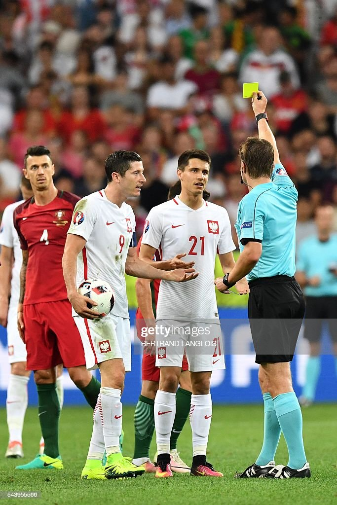 Poland's midfielder Bartosz Kapustka (C) receives a yellow card from German referee Felix Brych (R) during the Euro 2016 quarter-final football match between Poland and Portugal at the Stade Velodrome in Marseille on June 30, 2016. / AFP / BERTRAND
