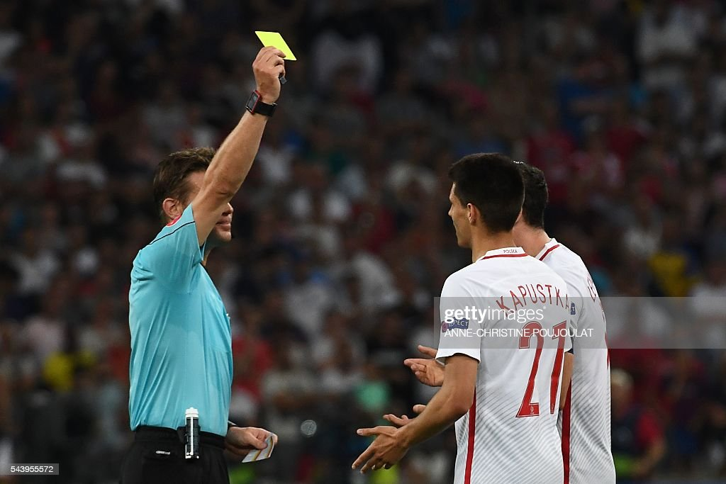 Poland's midfielder Bartosz Kapustka (R) receives a yellow card from German referee Felix Brych (L) during the Euro 2016 quarter-final football match between Poland and Portugal at the Stade Velodrome in Marseille on June 30, 2016. / AFP / ANNE