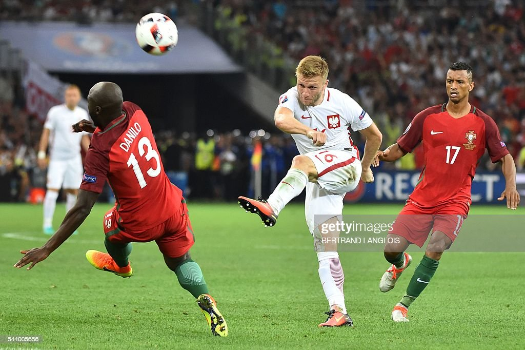 Poland's midfielder Jakub Blaszczykowski (C) kicks the ball next to Portugal's midfielder Danilo Pereira (L) and Portugal's forward Nani (R) during the Euro 2016 quarter-final football match between Poland and Portugal at the Stade Velodrome in Marseille on June 30, 2016. / AFP / BERTRAND