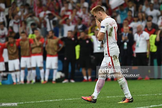 Poland's midfielder Jakub Blaszczykowski reacts after missing a shot in a penalty shootout during the Euro 2016 quarterfinal football match between...